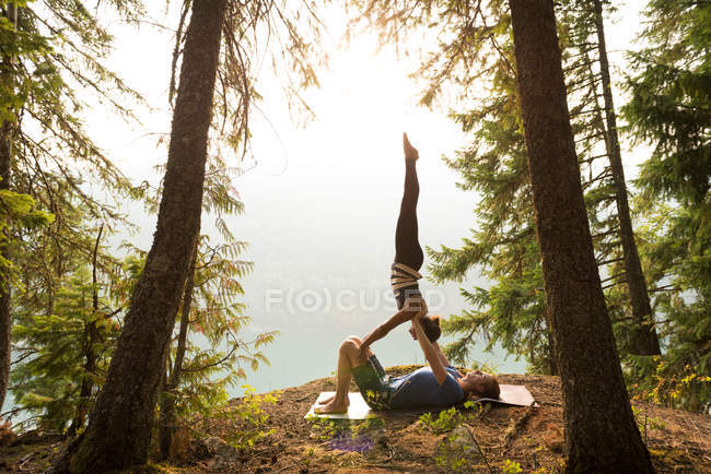 Sporty couple practicing acro yoga in a lush green forest at the time of dawn — Stock Photo