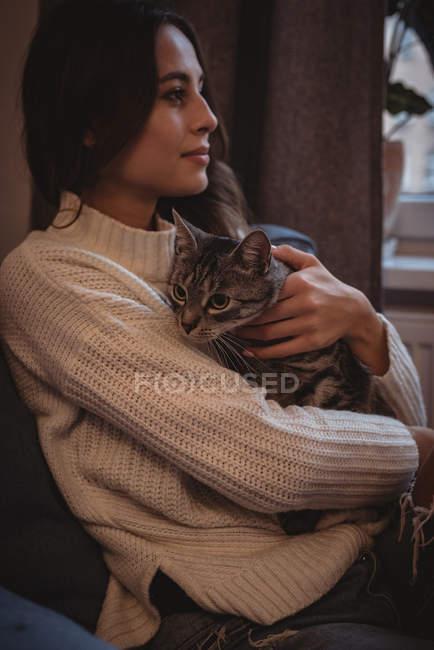 Мечтательная женщина обнимает своего домашнего кота дома — стоковое фото