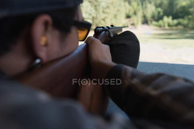 Close-up do homem apontando a arma no alvo no tiro ao alvo — Fotografia de Stock