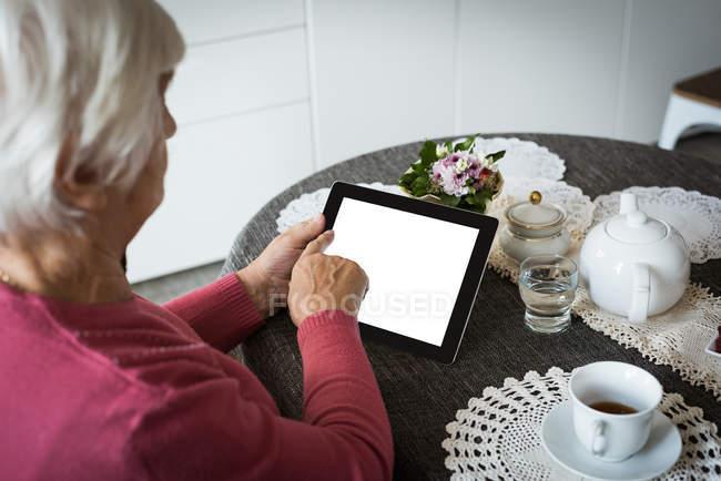 Seniorin nutzt Tablet im heimischen Wohnzimmer — Stockfoto