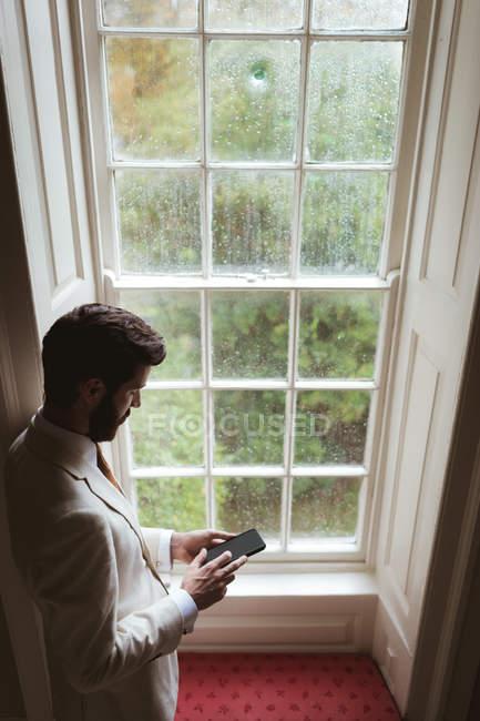 Groom usando seu telefone celular perto da janela em casa — Fotografia de Stock