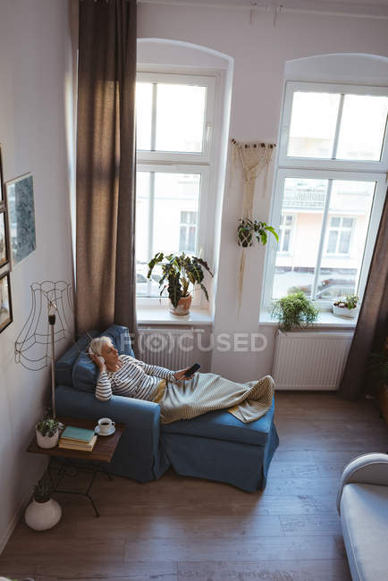 High angle view of senior woman relaxing on sofa with a smart phone listening to music at home — Stock Photo