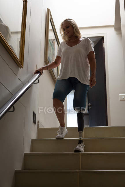Mature woman with prosthetic leg moving down stairs at home. — Stock Photo