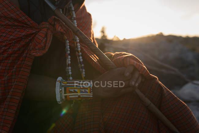 Розділ середині Масаї людина в традиційному одязі сидить з палицею — стокове фото