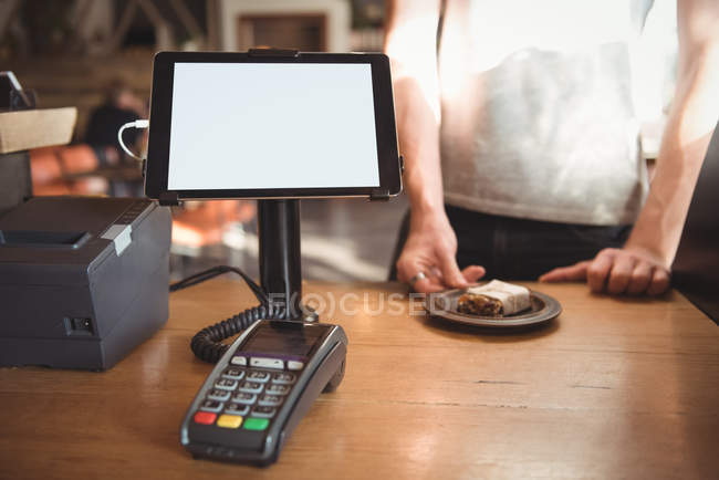 Mid section of waiter serving breakfast at counter of cafeteria — Stock Photo
