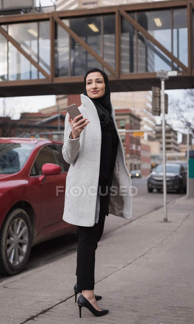 Woman in hijab using mobile phone on city street — Stock Photo