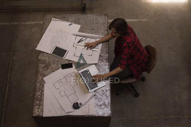 Young female engineer using laptop in workshop. — Stock Photo