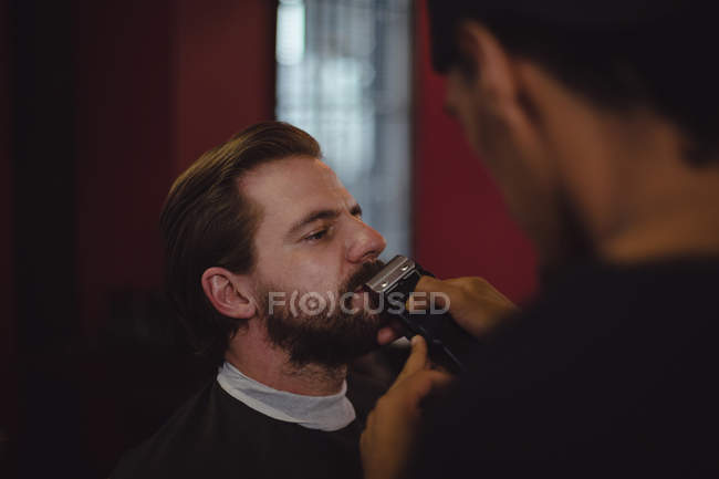 Man getting his beard trimmed with trimmer at barbershop — Stock Photo