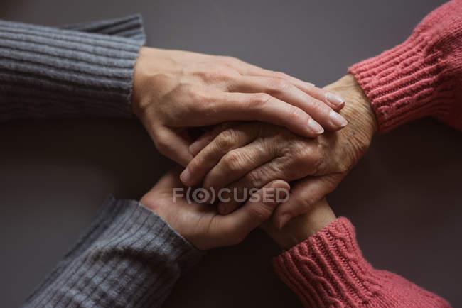 Крупный план смотрителя, утешающего пожилую женщину в доме престарелых — стоковое фото
