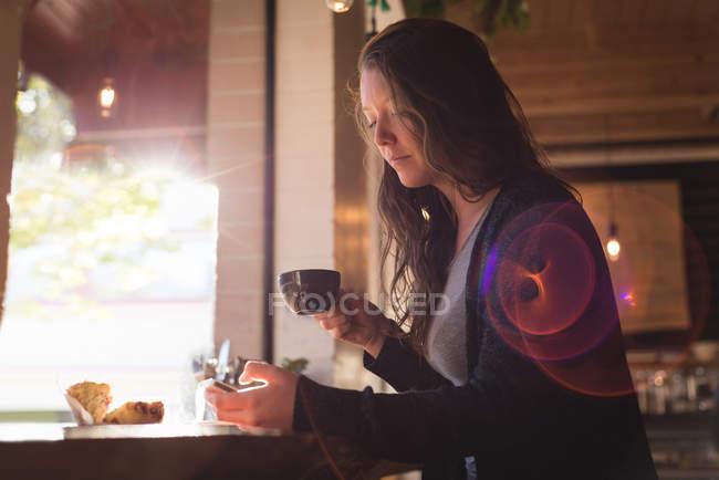 Женщина, с помощью мобильного телефона, имея кофе в кафе — стоковое фото