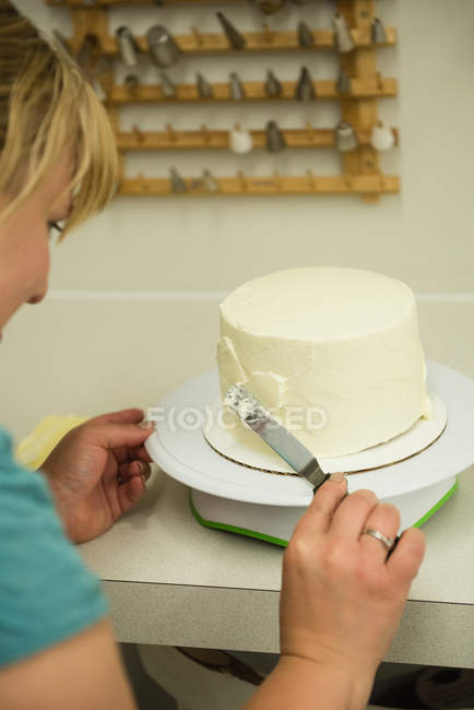 Close-up of woman preparing cake in bakery — Stock Photo