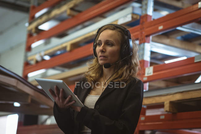 Female worker using digital tablet in factory — Stock Photo