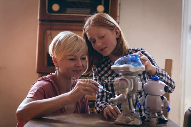 Mutter und Tochter reparieren das Roboterspielzeug zu Hause — Stockfoto