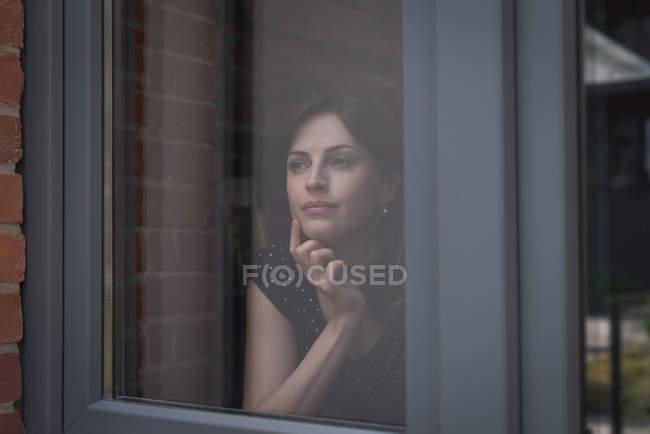 Esecutivo femminile guardando attraverso la finestra in ufficio — Foto stock