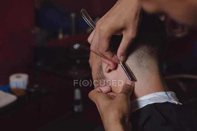 Мужчина стрижёт волосы бритвой в парикмахерской — стоковое фото