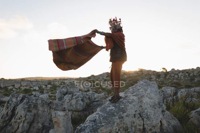 Масаї людина в традиційному одязі стоячи з шаль на скелі — стокове фото