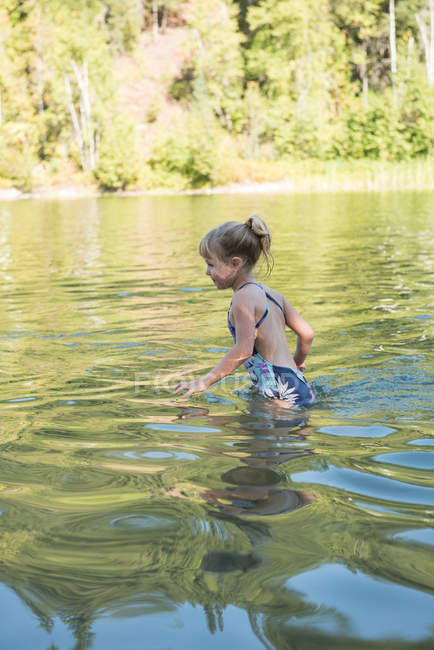 Happy girl playing in river on a sunny day — Stock Photo