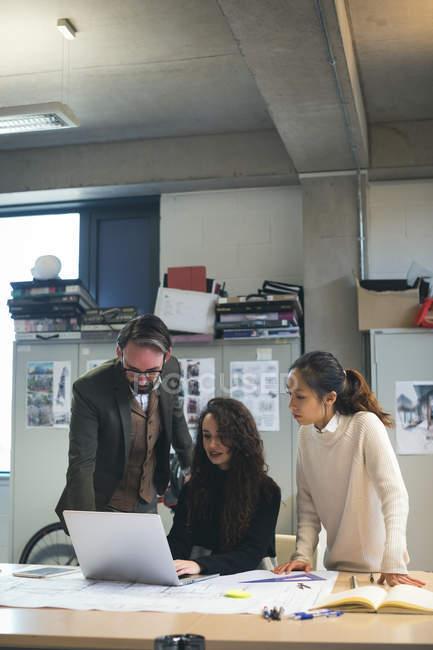 Руководители обсуждают за ноутбуком в современном офисе — стоковое фото