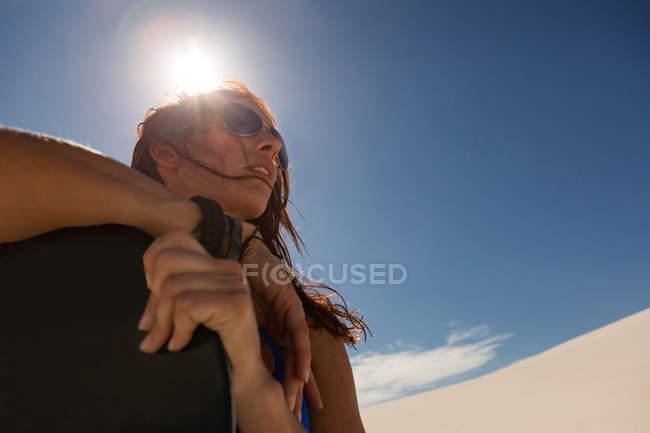 Donna con lavagna in piedi nel deserto in una giornata di sole — Foto stock