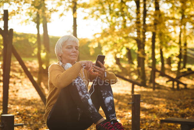 Femme âgée utilisant son téléphone portable dans le parc par une journée ensoleillée — Photo de stock