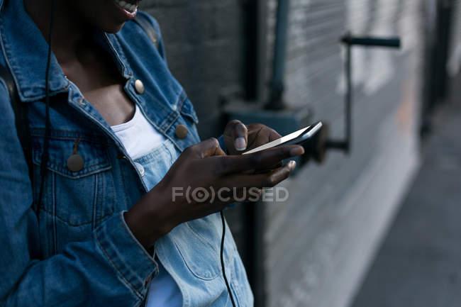Розділ середині жінці за допомогою мобільного телефону на тротуарі — стокове фото