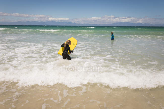 Siblings ready to surf in sea on a sunny day — Stock Photo