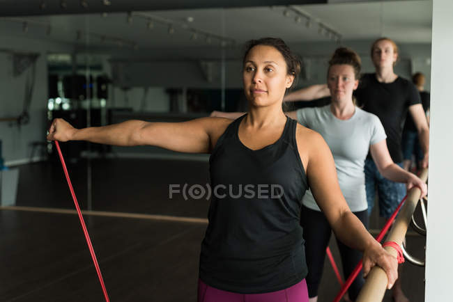 Fit people exercising with resistance bands in fitness studio. — Stock Photo
