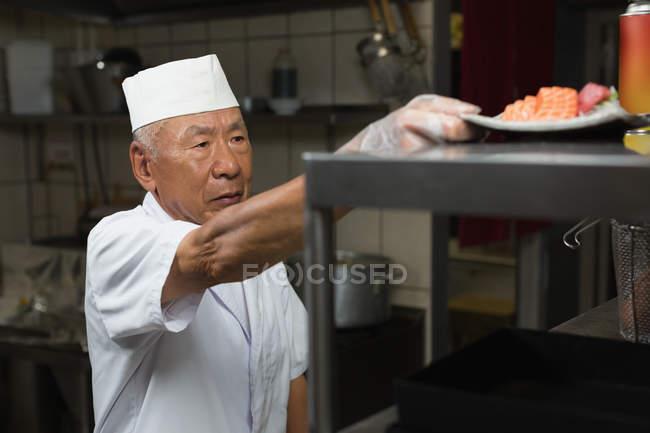 Старший повар Холдинг пластины суши в кухне на restauant — стоковое фото