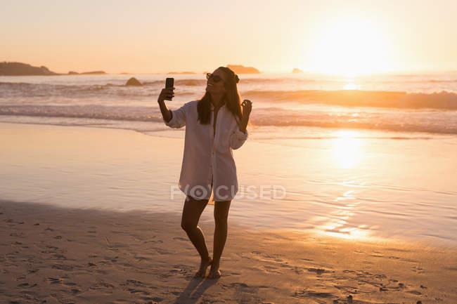 Mulher tomando selfie com telefone móvel na praia ao entardecer — Fotografia de Stock