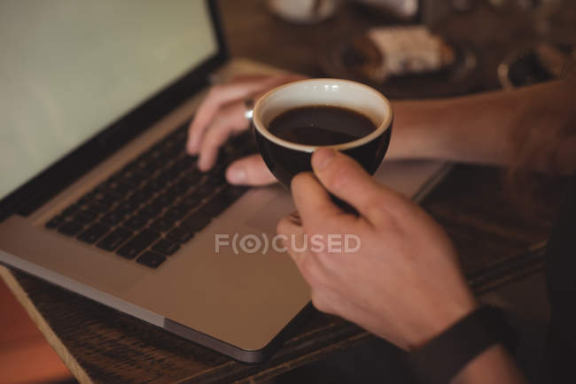Close-up of man using laptop while having coffee in cafe — Stock Photo