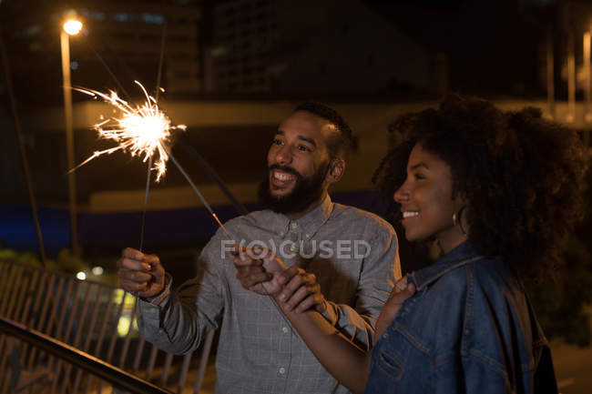 Smiling couple playing with sparkles at night — Stock Photo