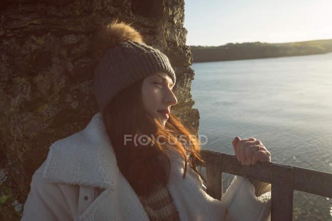 Donna premurosa appoggiata sul muro di pietra vicino al lungofiume in luce morbida . — Foto stock