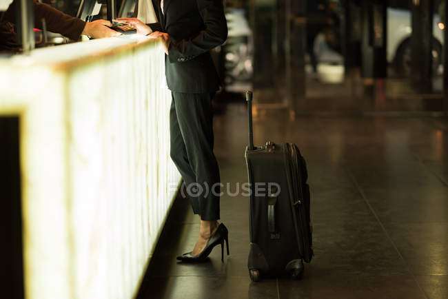 Businesswoman standing at reception wit her baggage in the hotel — Stock Photo