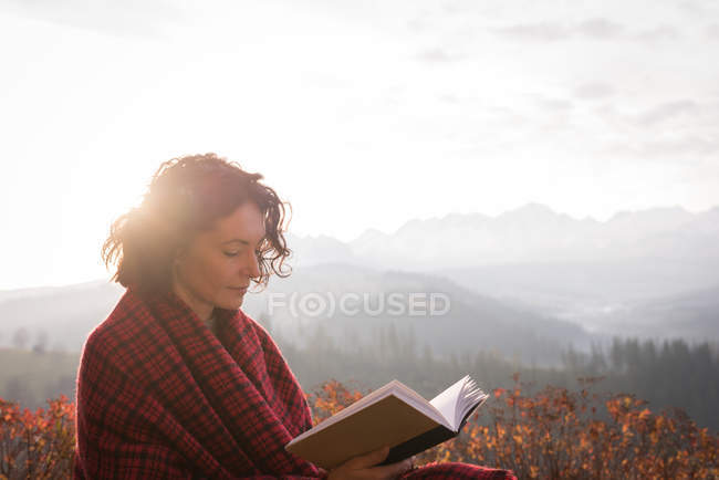 Frau in Decke gehüllt liest Buch an nebligem Tag — Stockfoto