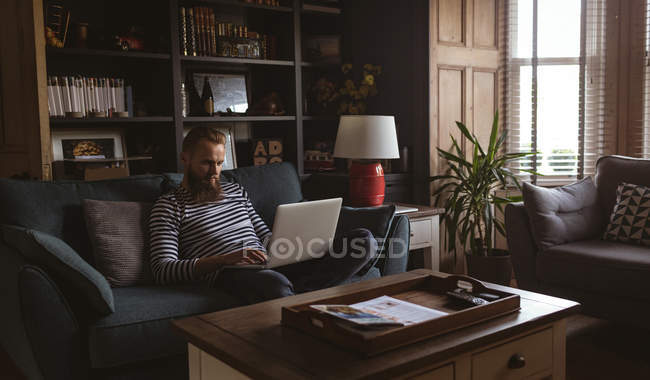 Man sitting on sofa using his laptop at living room — Stock Photo