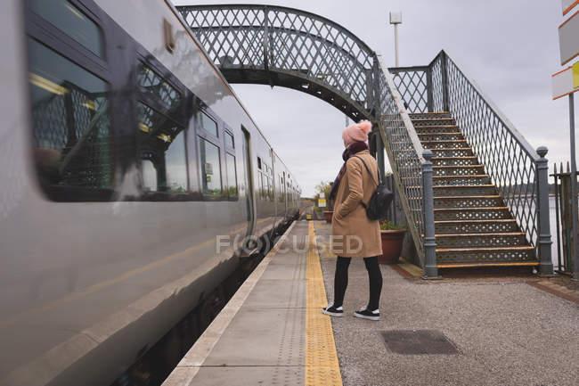 Vista posteriore della donna che aspetta il treno nella