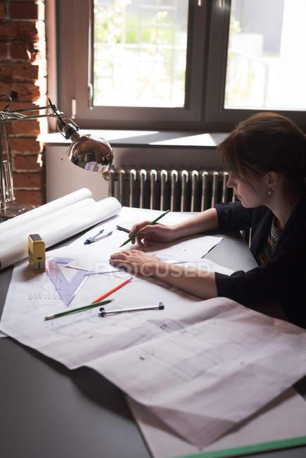 Esecutivo femminile lavorando su blueprint in ufficio — Foto stock