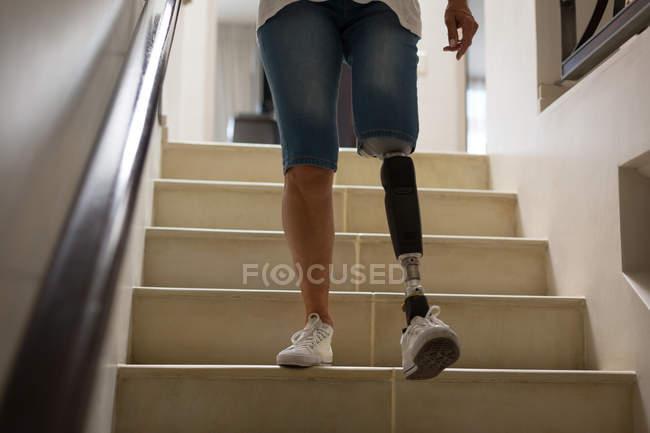 Обрезанный вид женщины с протезной ногой, движущейся вниз по лестнице дома . — стоковое фото