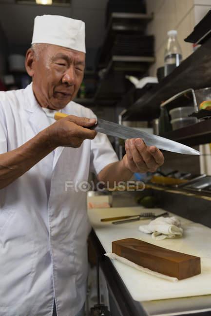Старший повар, держа нож на кухне отеля — стоковое фото