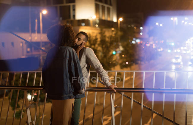 Romantic couple kissing each other while standing near railing at night — Stock Photo