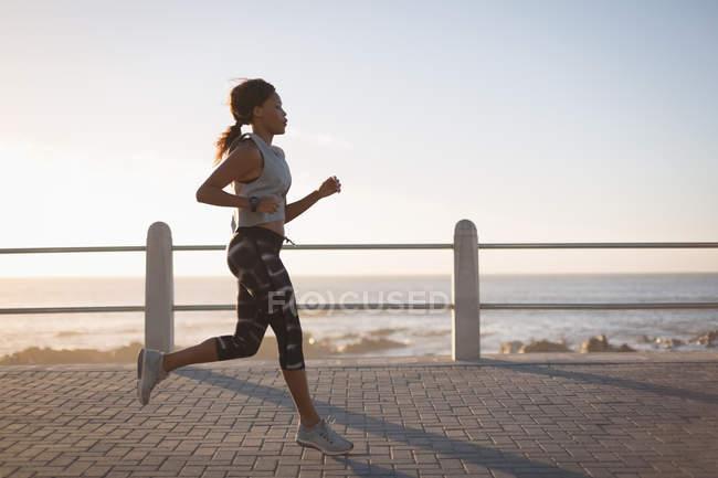 Mulher jovem, movimentando-se perto da praia durante o pôr do sol — Fotografia de Stock