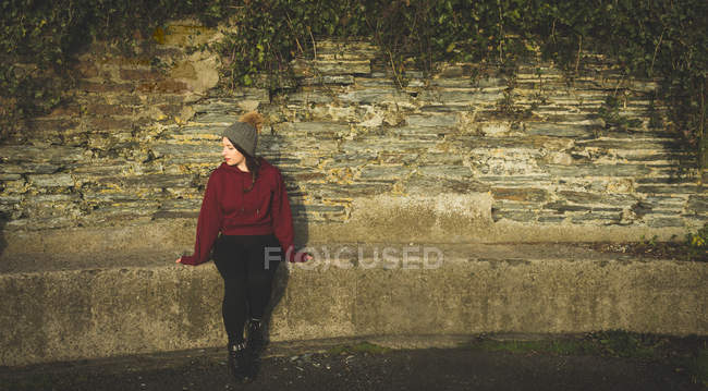 Donna rilassante contro la parete alla luce del sole . — Foto stock