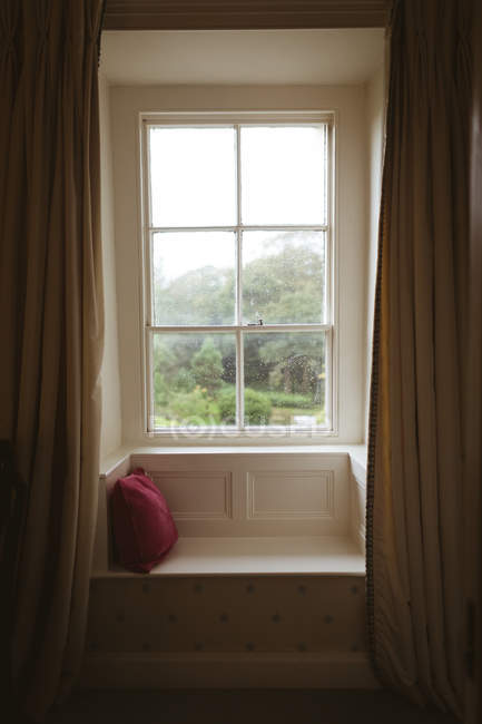 Seating area and a cushion near the window at home — Stock Photo