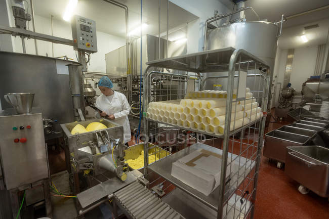 Female worker monitoring batter in a machinery in the food factory — Stock Photo