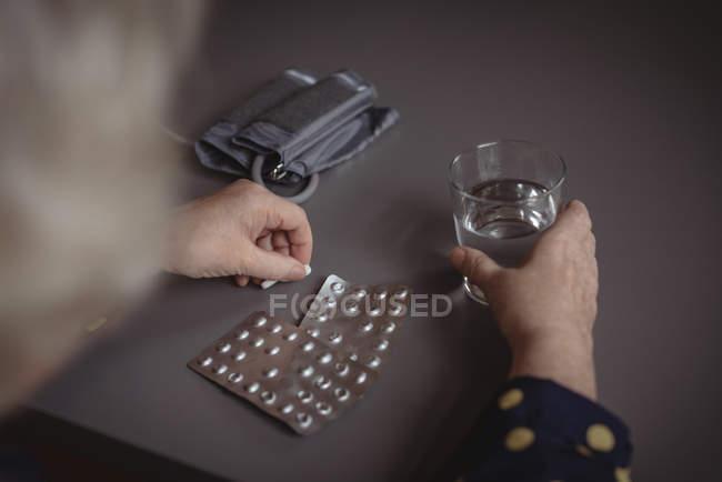 Sección media de mujer sentada con pastillas y vaso de agua - foto de stock