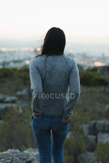 Vista traseira da mulher em pé com a mão no bolso — Fotografia de Stock