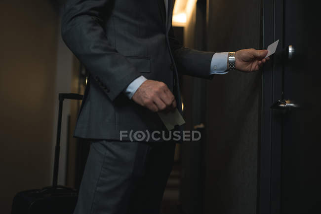 Cropped image of businessman holding access card in hotel — Stock Photo