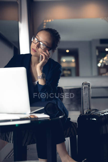 Woman talking on mobile phone while using laptop at table — Stock Photo