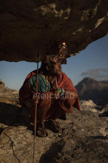 Масаї людина в традиційному одязі сидить з палицею на скелі — стокове фото