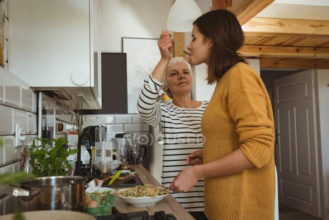 Старші жінки ложка годування дочка перевірити смак на кухні під час приготування їжі — стокове фото